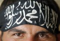 "File photo shows a Free Syrian Army fighter wearing a headband reading the Islamic declaration of faith, ""There is no God but God, and Mohammed is His Messenger"", in central Aleppo"